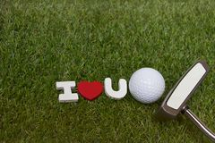 Golf ball and putter with I love you sign on green course. Golf ball and putter with I love you wooden sign are on green grass Stock Photos