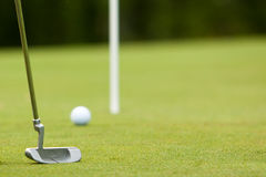 Golf ball and putter near green and flag Royalty Free Stock Image