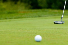 Golf ball and putter near green Royalty Free Stock Photography