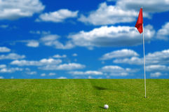 Golf ball on the putting green. With sky and clouds in the background royalty free stock images