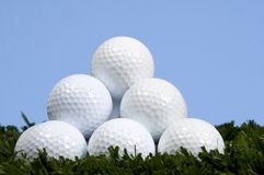 Golf Ball Pyramid on grass against blue sky. Golf ball pyramid on grass with blue sky stock image