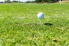 Golf ball ready to tee off on top of tee at golf course stock photography