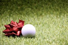 Golf ball with red ribbon Royalty Free Stock Photos
