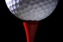 Golf Ball on Red Tee. Horizontal macro view of a golf ball on a red tee with a black background royalty free stock image
