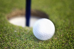 Golf ball rolling into hole stock image