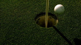 Golf ball rolling into the hole on putting green stock video