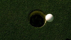 Golf ball rolling into the hole on putting green. In slow motion stock video footage