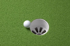 Golf ball rolls to hole Royalty Free Stock Photo