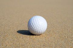 A golf ball in the sand. Stock Photography