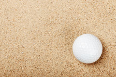 Golf ball on the sand Royalty Free Stock Photo