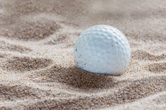 Golf ball in sand bunker Royalty Free Stock Image