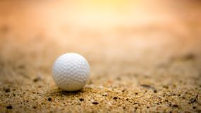 Golf ball on sand in golf course on sunset royalty free stock photo