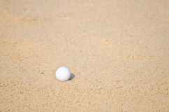Golf ball. In a sand trap Stock Photography