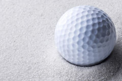 Golf ball in sand trap Stock Photos