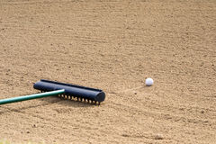 Golf ball in a sand trap with a rake Royalty Free Stock Photos