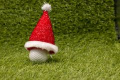 Golf ball and Santa hat on green grass. Golf ball and tee on green grass, idea for golfing concept stock photo