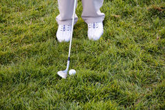 Golf ball, shoes and driver in the grass Royalty Free Stock Images