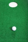 Golf ball short of hole. On artificial turf Royalty Free Stock Photos