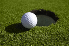 Golf Ball Sits At The Edge Of The Hole Royalty Free Stock Photo