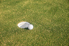 Golf ball sits at the lip of the hole on the putting green. Royalty Free Stock Photos