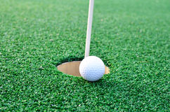 Golf ball sits at the lip of the hole on the putting green Royalty Free Stock Photos