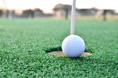 Golf ball sits at the lip of the hole on the putting green Royalty Free Stock Photo