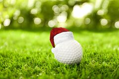 Golf ball with small Santa hat on course