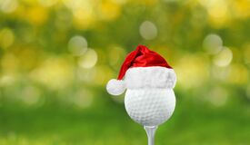 Golf ball with small Santa hat on tee against background
