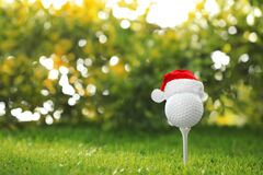 Golf ball with small Santa hat on tee against background. Space for text