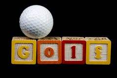 Golf ball and spelled out. Golf Ball sitting on top of the leters GOLF stock photo