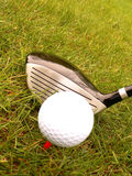 Golf ball and stick. In the grass stock photos
