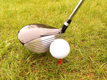 Golf ball and stick. In the grass royalty free stock image