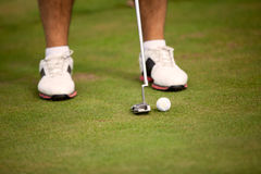 Golf ball and stick with golfer legs in background Stock Photo
