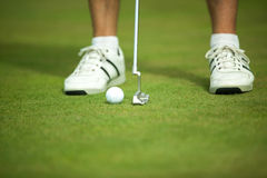 Golf ball and stick with golfer legs in background Stock Photography