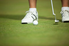Golf ball and stick with golfer legs in background Royalty Free Stock Photo