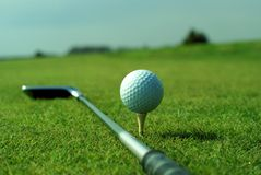 Golf ball in tall green grass set against blue sky Royalty Free Stock Photo