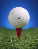 Golf ball on tee. Gol fball on tee with grass and sky Royalty Free Stock Images