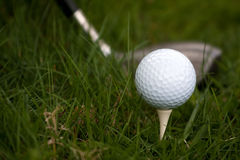 Golf Ball and Tee. A white golf ball set up on the tee with a driver about to swing. Shallow depth of field stock image
