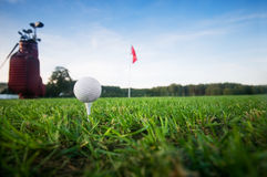 Golf ball on tee. Green grass, sunset sky Stock Photos