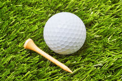 Golf Ball and Tee. Closeup of golf ball and tee on grass Stock Photo