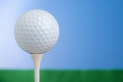 Golf Ball On Tee 2. A horizontal shot of a golf ball resting on a tee. Grass and sky fill the background royalty free stock photos