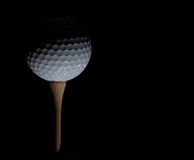 Golf ball on tee. White Golf ball on a tee on dark background Royalty Free Stock Photo