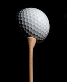 Golf ball on tee. White Golf ball on a tee on dark background Stock Photography