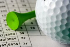 Golf Ball and Tee. Close-up golf ball and tee on a scorecard (shallow dof Stock Photo