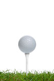 Golf ball on tee. Golf ball on a tee viewed from surface level, high key studio shot using real grass stock photography