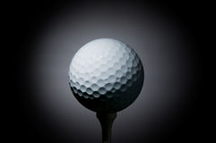 Golf ball on tee. Illuminated by a ray of light on black background. Welcome to the PGA tour! Space for text stock image