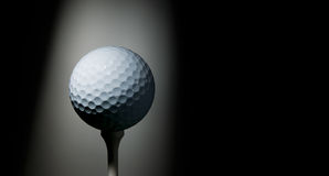 Golf ball on tee. Illuminated by a ray of light on black background. Welcome to the PGA tour! Space for text Royalty Free Stock Image