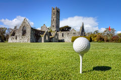 Golf ball on the tee in Adare, Ireland. Golf ball on the tee - idyllic golf course of Adare and Franciscan Abbey in the background in Ireland Stock Photos