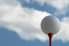 Golf ball on tee against cloudy sky. Golf ball on red tee against cloudy sky Stock Photo