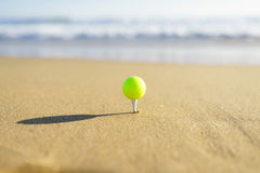 Golf Ball on a tee at a California beach with white wave in Pacific Ocean Stock Images